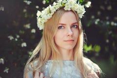 Attraktiv blygsam ung flicka med blondinen med jasminblommakransen på head långt hår och naturligt smink i den vita klänningen ut arkivbild