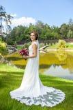 Attraktiv brud i hållande bouque för härlig klänning för bröllop vit arkivbilder