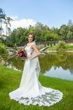 Attraktiv brud i hållande bouque för härlig klänning för bröllop vit royaltyfri foto
