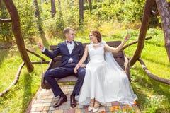 Attraktiv brud med brudgumsammanträde på trägunga bland träd arkivfoto