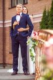 Attraktiv brud som kramar den stiliga brudgummen, medan stå på bron arkivbilder