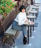 Attraktiv brunett för kvinna att äta gourmet- bakgrund för kakakaféterrass Gastronomical njutning Flickan kopplar av kafét med ka royaltyfri foto