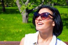 Attraktiv brunett i solglasögon som skrattar i parkera på en solig dag Royaltyfri Bild