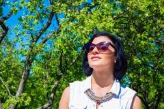 Attraktiv brunett i solglasögon som vilar i parkera Fotografering för Bildbyråer