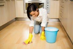 Attraktiv brunett som gör ren golvet Royaltyfri Foto