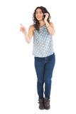 Attraktiv brunett som pekar på något, medan ha påringning Royaltyfri Bild