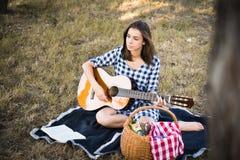 Attraktiv brunett som spelar gitarren och att tänka Arkivbild