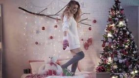 Attraktiv brunettdans på en säng i röda tumvanten nära en julgran stock video