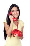 Attraktiv brunettflicka som kallar med den röda telefonen Royaltyfri Bild