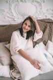Attraktiv brunettkvinna i tappninghemmiljö Härlig kvinnlig modell i en vit tröja som sitter på soffan på vit royaltyfri bild