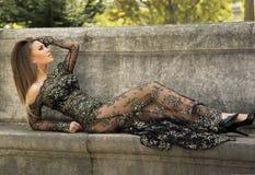 Attraktiv brunettskönhet som poserar i elegant klänning. Royaltyfri Foto
