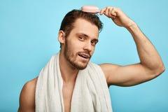 Attraktiv brutal sexig man som använder en hårkam royaltyfria foton