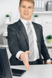 Attraktiv business man giving a hand in office Stock Photo