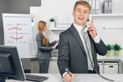 Attraktiv business man speaking at telephone in office Stock Image