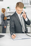 Attraktiv business man speaking at telephone in office Royalty Free Stock Image