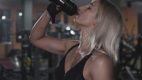 Attraktiv caucasian flicka som dricker proteinskakadrinken i sportidrottshall i slowmo stock video