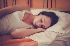 Attraktiv caucasian flicka som sover på sängen arkivfoton