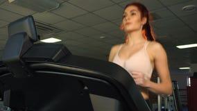 Attraktiv caucasian flickaspring på trampkvarnen i sportidrottshallen stock video
