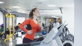 Attraktiv caucasian flickaspring på trampkvarnen i sportidrottshallen, 4k stock video