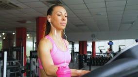 Attraktiv caucasian flickaspring på trampkvarnen i sportidrottshallen med hörlurar stock video