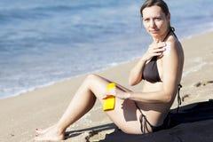 Attraktiv caucasian kvinna som sätter lotion på hennes kropp Fotografering för Bildbyråer
