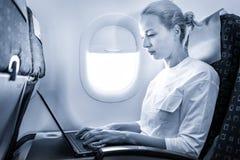 Attraktiv caucasian kvinnlig passagerare som arbetar p? den moderna b?rbar datordatoren genom att anv?nda tr?dl?s anslutning ombo arkivfoto