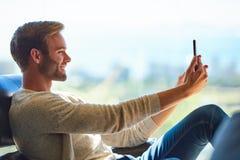 Attraktiv caucasian man som tar en selfie med hans mobiltelefon arkivfoto