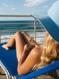 attraktiv chaiselongue kopplar av kvinnan Arkivfoto