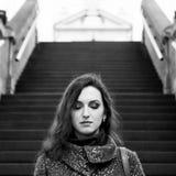 Attraktiv dam med stängda ögon, långt hår, sinnliga kanter och yrkesmässigt makeupanseende på gatan Svart och arkivfoto