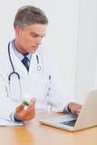 Attraktiv doktor som rymmer en flaska av preventivpillerar arkivbilder