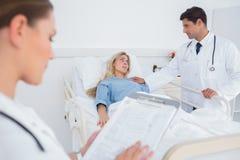 Attraktiv doktor som tar omsorg av en tålmodig Fotografering för Bildbyråer