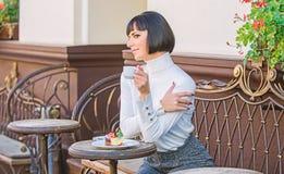 Attraktiv elegant brunett f?r kvinna att ?ta gourmet- bakgrund f?r kakakaf?terrass Angen?m tid och avkoppling l?ckert royaltyfri foto