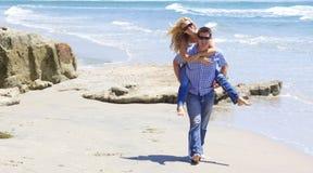 Attraktiv för par ritt på ryggen på stranden Royaltyfri Bild