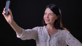 Attraktiv förtjusande ung kvinna som tar selfie och ler på telefonkameran som isoleras på svart studiobakgrund lager videofilmer