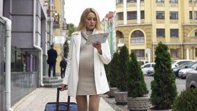 Attraktiv förväntande kvinnlig med resväskan som söker efter kliniken i staden, lopp arkivbild