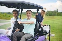 Attraktiv familj i deras golfvagn Arkivfoton