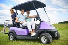 Attraktiv familj i deras golfvagn Arkivbild