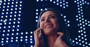 Attraktiv flicka för nära övre stående som talar på telefonen och skratten lager videofilmer