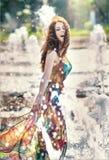 Attraktiv flicka i den mångfärgade korta klänningen som spelar med vatten i en varmmast dag för sommar Flicka med den våta klänni Arkivfoto