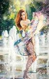 Attraktiv flicka i den mångfärgade korta klänningen som spelar med vatten i en varmmast dag för sommar Flicka med den våta klänni arkivfoton