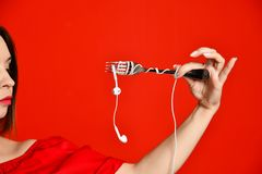 Attraktiv flicka i den röda klänningen som rymmer en gaffel i händer på headphoneproppen Förberett att äta royaltyfri foto