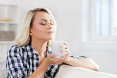 Attraktiv flicka i en skjorta som tycker om en kopp kaffe Royaltyfria Bilder