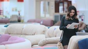 Attraktiv flicka i en svart klänning som går på möblemanglagret som rymmer en minnestavla i händer arkivfilmer