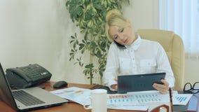 Attraktiv flicka i kontoret som talar på en cell arkivfilmer