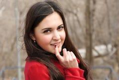 Attraktiv flicka i rött lag och hennes skämtsamma blick Royaltyfria Foton