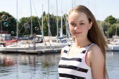 Attraktiv flicka i randig klänning på sjösidan Royaltyfri Foto