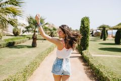 Attraktiv flicka i rolig dans för bra form med hår som vinkar och skrattar som tycker om sommarsemester i exotiskt land arkivbild