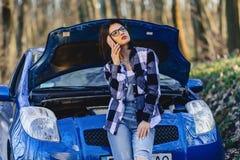 attraktiv flicka med den near öppna huven för telefon av bilen arkivfoto