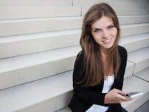 Attraktiv flicka med den smarta telefonen Arkivfoto