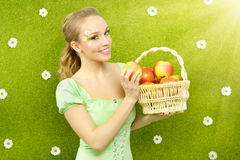 Attraktiv flicka med en korg av äpplen arkivfoton